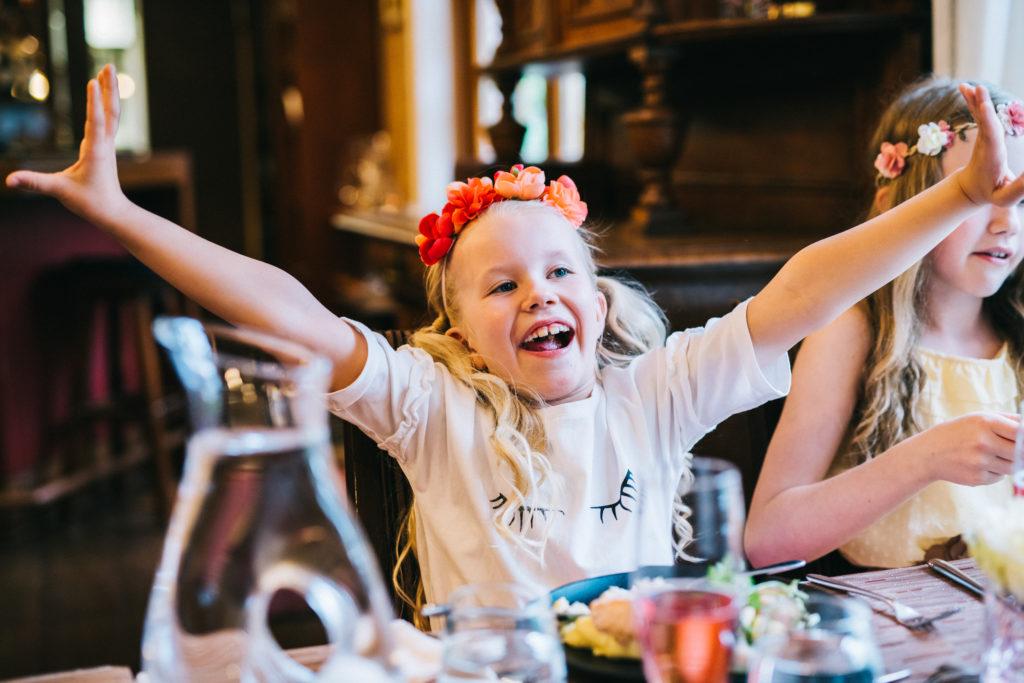 Hymyilevä lapsi kurottelee käsillä ylös ravintolapöydän ääressä.