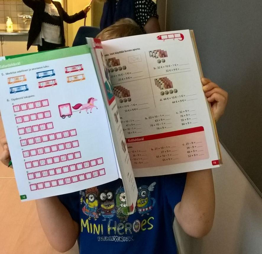 Lapsi pitelee auki olevaa koulukirjaa kasvojensa edessä.
