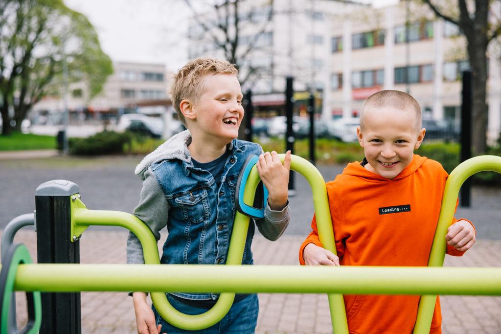 Kaksi poikaa nauraa ja leikkii yhdessä leikkipuistossa.