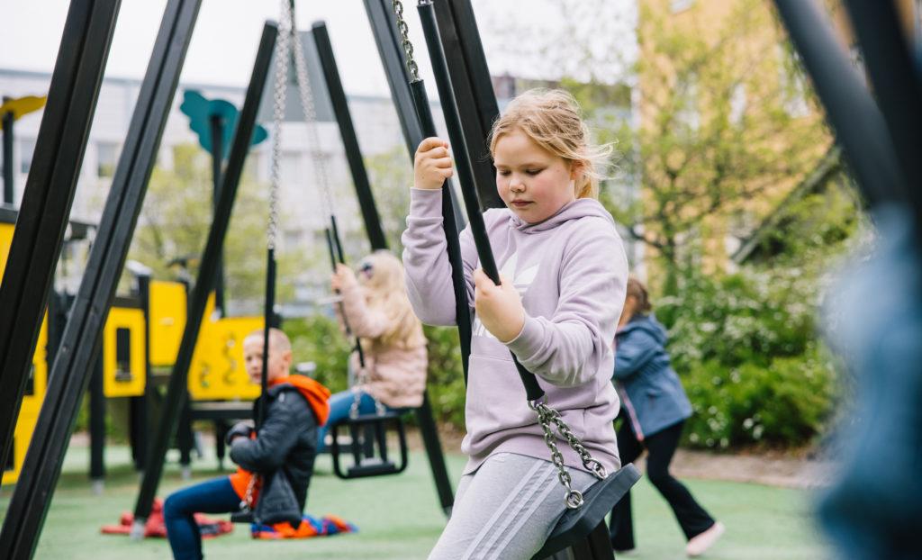 Lapset keinuvat leikkipuistossa, etualalla oleva tyttö näyttää olevan allapäin.
